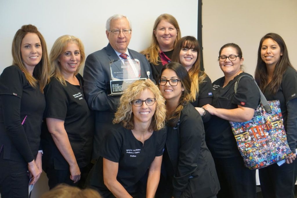 At Los Robles Hospital receiving the Frist Humanitarian Award, accompanied by his office staff.
